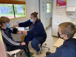 Frau Tapper von der JadeBay GmbH erklärt zwei Schülern der Klasse 10b das Blutdruckmessen.